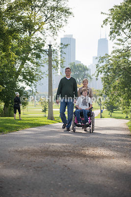 Parents With Their Daughter With a Disablility  Walking At Park