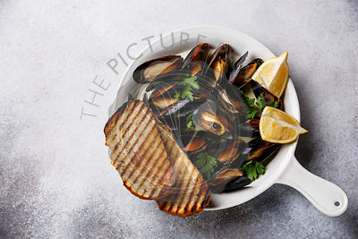 Mussels in white dish pan with parsley, toasted bread and lemon on white background
