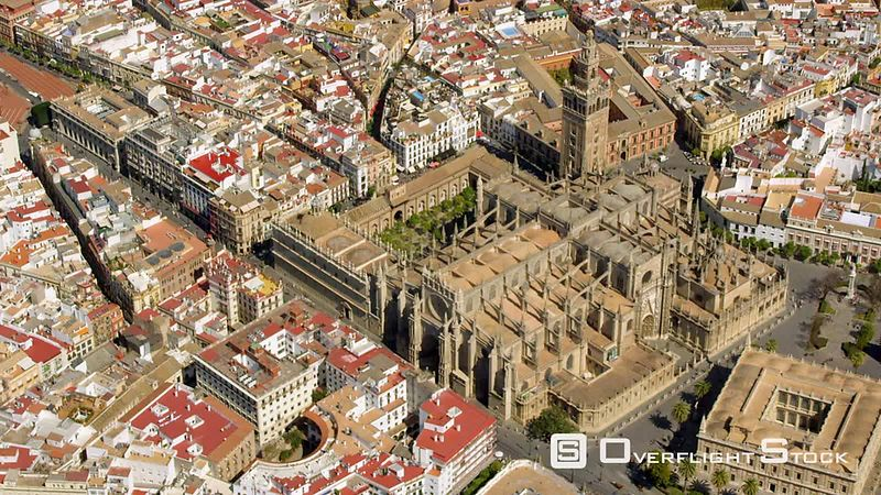 CIRCLING AERIAL VIEW OF SEVILLE CATHEDRAL WITH LA GIRALDA BELFRY AND THE ARCHIVOS DE LAS INDIAS THE GENERAL ARCHIVE OF THE INDIES THE SQUARE BUILDING TO THE RIGHT OF THE CATHEDRAL) SPAIN