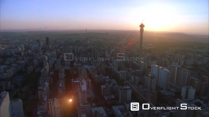 Aerial shot over Johannesburg Central Business District with the Hillbrow Tower towering above and passing the Ponte Tower during sunset/sunrise. Johannesburg Gauteng South Africa