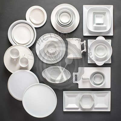 Assorted variety of white porcelain dinnerware laid out in a grpahic, organized way on a gray background.