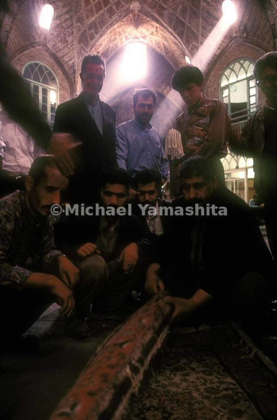 A group of men negotiate the purchase of a silk carpet in Tabriz market.