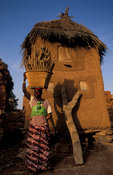 Woman carrying millet to a granary, Songo, Dogon Country, Mali