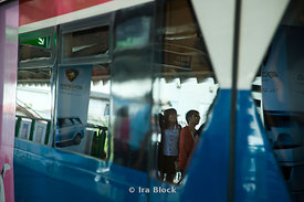 An abstract view of the BTS Skytrain with a few travelers located in Bangkok, Thailand.