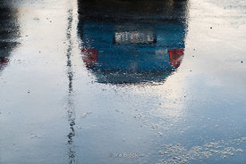 A reflection of a car on a sheet of ice in Iceland.