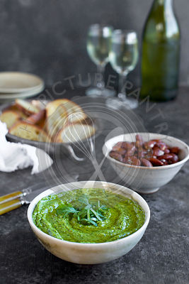 Arugula Chive Basil Pesto served in a ceramic bowl with crostini, almonds and wine.  Photographed fron front view on a black/brown background.