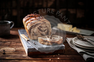 Warm loaf of chocolate braided bread on a marble board in a rustic wood setting.