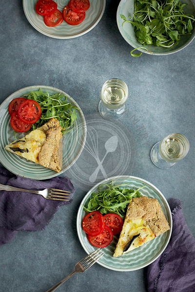 Potato Sage Gruyere Galette served with tomatoes, arugula and white wine.  Photographed on a grey background from top view.
