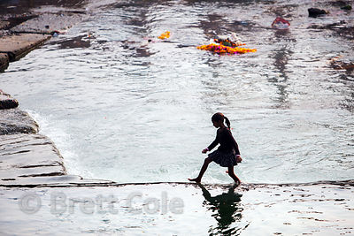 A girl walks across a ghat in the Ganges River, Haridwar, India