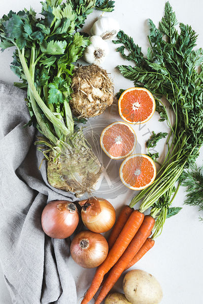 celery root, sliced oranges, carrots, and onions are photographed from the top view.