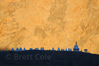 Stupas against a golden mountain face near Phyang Gompa, Phyang, Ladakh, India