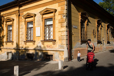 Hungary - Pecs - A mother and child walks past typical Nineteenth century architecture