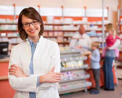 Smiling pharmacist standing in store