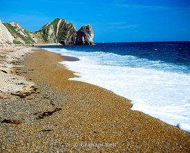 beach with durdle door in the distance, dorset.