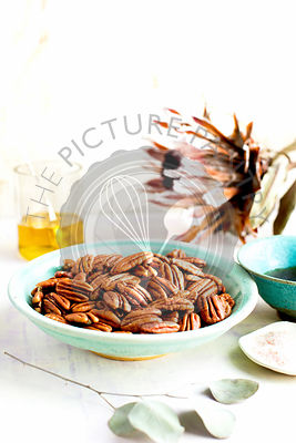 Caramelized Pecans. Photographed on a lavender/white background.