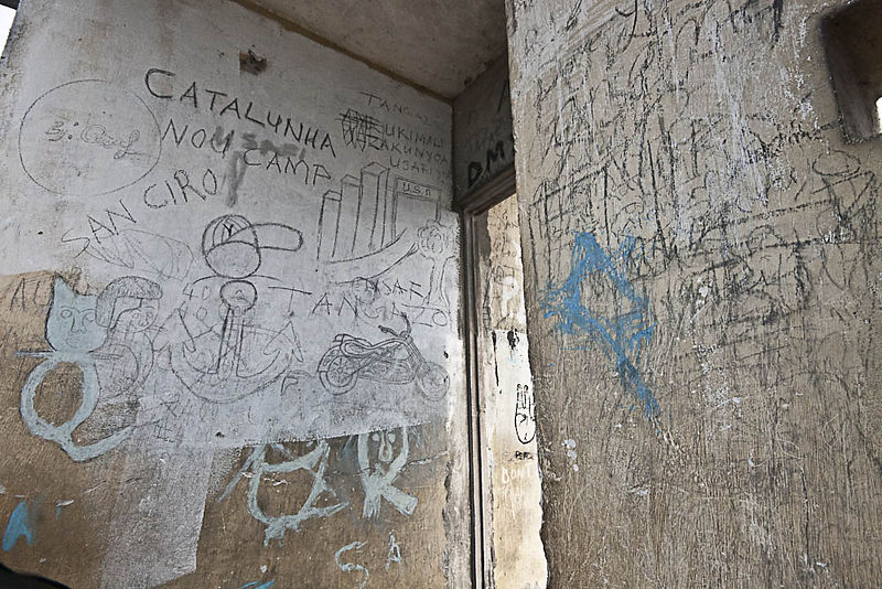 "The external walls of the flats are famous locally for their graffiti. The 1968 plan was accompanied by a propaganda blitz of posters, banners, and radio broadcasts to project its ideological vision of the cityscape. A widely circulated pamphlet in Kiswahili came with pictures of the apartments that supposedly offered ""the workers better living conditions and [saved] them from living in lousy huts -- the poor state in which the colonialists left us"" (Zanzibar National Archives)."