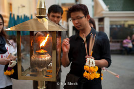 Worshippers light incense at the Erawan Shrine.