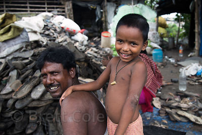 Father and son at a rubber shoe recycling operation, Dhapa, Kolkata, India. Dhapa is a large industrial zone that processes most of Kolkata's garbage and recycling.