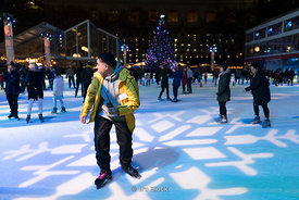 People skating on the ice rink at Bryant Park Winter Village in Manhattan, New York
