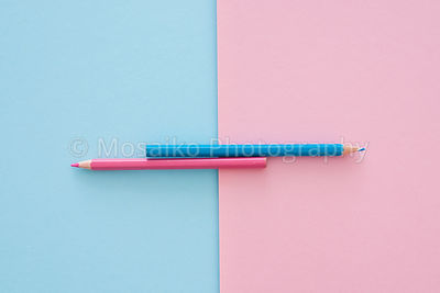 blue and pink pencils on pink and blue paper background