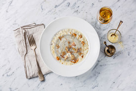 Risotto with chanterelle mushroom on plate on white marble table background