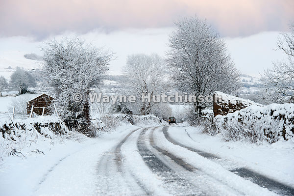 Rural road covered in snow, making it hard to travel. Wensleydale, North Yorks, UK
