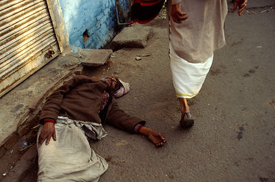 India - New Delhi - A man lies drunk in an alleyway
