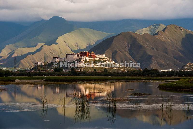 A reflection of the Potala Palace, which towers 100 meters (300 feet) above Lhasa, floats among the mountains and the marsh that spreads out behind this most iconic of Tibet's ancient monasteries.