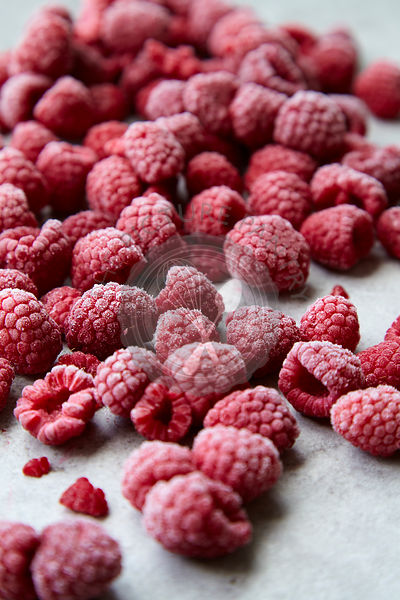 Frozen raspberries on grey stone background