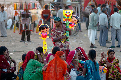 A woman in traditional dress holding Spongebob and Dora the Explorer balloons, Pushkar, Rajasthan, India