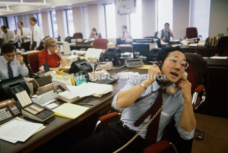 Man in the middle, gold trader Alan Yamashita has his hands full at Goldman Sachs & Company in New York City as he talks with a buyer on one phone and a seller on the other. Holder of degrees from Yale and Princeton, Yamashita, 35, now oversees the company's foreign exchange and commodities business in Tokyo.