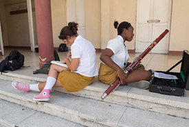 Students of the Benny Moré Art School in Cienfuegos, Cuba playing the fagotto or bassoon, and studying on a porch.