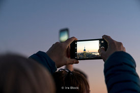 A person photographing The Empire State Building from the top of the Rockefeller Center in New York City.