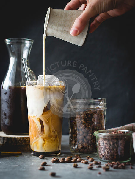 Woman pouring milk in to an iced coffee