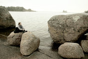 Woman sitting on round boulders by the sea