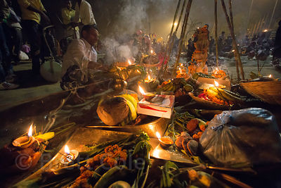 Offerings on the banks of the Ganges River during Chhath Puja, Varanasi, India. Chhath Puja is a devotion to the Sun God Surya in which people gather at sunset and then on the following sunrise and offer prayers.