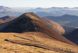 The winding path up to the summit of Sail and Scar Crags in the distance in the English Lake District, UK.