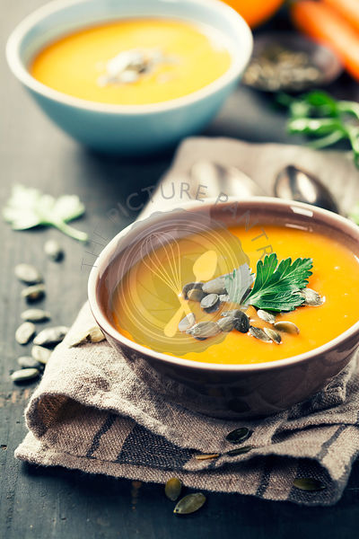Pumpkin soup in a bowl on a wooden surface