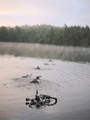 Adventure racers swimming with bike