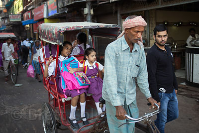 Girls are driven to school on a cycle rickshaw, Chandni Chowk, Delhi, India
