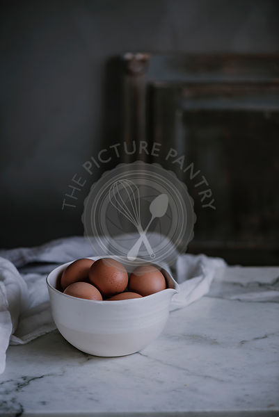 Eggs in a bowl on a marble worktop in a rustic kithcen