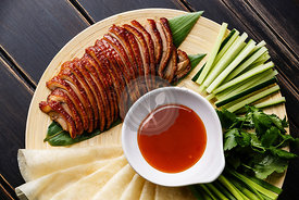 Sliced Peking Duck served with fresh cucumber, green onions, cilantro and roasted wheaten chinese pancakes with Hoysin sauce close-up