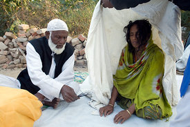 India - New Delhi - A Sufi holy man or Pir, exorcises a spirit from a woman at a dargah or shrine in South Delhi..