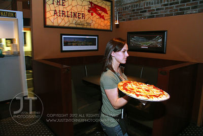 Server Erin Beal delivers pizza to a table at the Airliner Bar, 22 S Clinton Street in downtown Iowa City Saturday night. Copyright Justin Torner 2012 http://justintorner.photoshelter.com