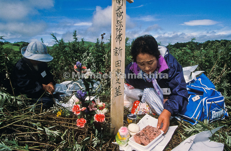 The Japanese return, if only for a day, to tend the overgrown graves of their ancestors. On Shikotan, Setsu Nitta leaves offerings of red rice, sake, and flowers on her father-in-law's plot. She last knelt here as a young woman, one of 17,000 Japanese expelled by Soviet troops by 1949.