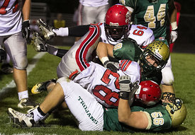 Iowa City West's Ezra Reiners (9) and Ben Hilmer (56) tackle Iowa City High's Bryson Runge (28) during the Battle for the Boot at Iowa City West Friday night, October 5, 2012. (Justin Torner/Freelance)