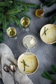 Asiago White Bean Soup with Thyme Oil served in ceramic bowls with white wine.  Photographed from top view on a gray background.