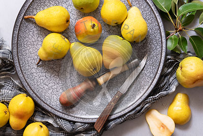 Ripe William pears on a plate with a knife and an apple corer.