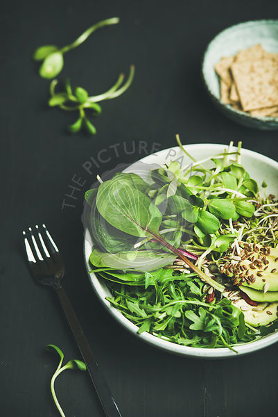 Green vegan breakfast meal in bowl with spinach, arugula, avocado, seeds and sprouts over black background