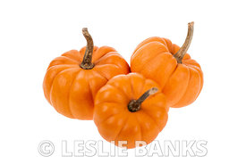 Three small orange pumpkins isolated on white